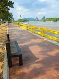 Houten parkbank op de rode manier van de baksteenweg met toneel de bergmening van de waterkant in Krabi, Thailand stock foto's