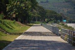Houten parkbank op de rode manier van de baksteenweg met toneel de bergmening van de waterkant in Thailand Leeg, groen stock foto
