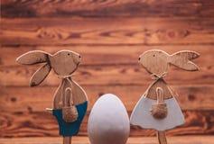 Houten Pasen-konijntjes die elkaar onder ogen zien dichtbij groot ei Stock Foto