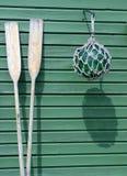 Houten peddels en een boei tegen een groene muur Stock Afbeeldingen