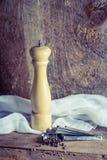 Houten peppermill, lepels en peperbollen op rustiek hout Royalty-vrije Stock Afbeeldingen