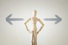 houten persoon die zich met zijn rug voor geweven hoogtepunt die als achtergrond van pijlen bevinden in verschillende richtingen  Stock Foto's