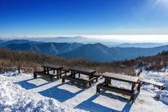 Houten picknicklijsten met banken in de winter, Deogyusan-Bergen, Korea Royalty-vrije Stock Foto