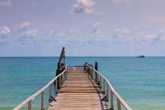 Houten pier die tot de zeekust leiden stock afbeelding