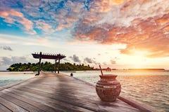 Houten pier op een blauwe oceaan bij zonsondergang stock foto's