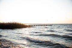 Houten pier op het meer Golven die op de kiezelsteenbank breken stock afbeelding