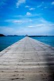 Houten pier op over het mooie strand met blauw Royalty-vrije Stock Afbeeldingen