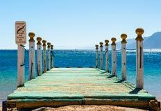 Houten pijler met kolommen en een waarschuwingsbord tegen een blauwe overzees en bergen op de horizon in van Zuid- Egypte Dahab S stock afbeelding