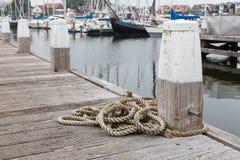 Houten pijler met meerpaal en kabel in Nederlandse haven Urk Stock Fotografie