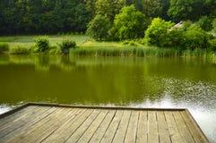 Houten pijler op een mooi bosmeer stock fotografie