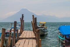 Houten pijler in Panajachel-dorp, Guatemala De vulkaan van San Pedro visibl stock foto's