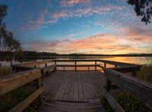 Houten pijler of pier op meerzonsondergang en het water van de hemelbezinning Stock Foto