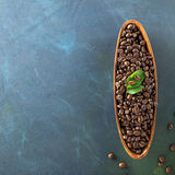 Houten plaat in de vorm van bonen van de boten de volledige donkere aromatische koffie op een kleurrijke blauwgroene achtergrond Stock Fotografie