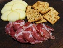 Houten plaat met kaas, ham en crackers stock foto