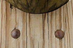 Houten plank met twee grote ronde spijkers stock fotografie