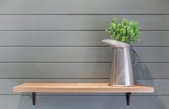 Houten plank op plankmuur met vaas van plastic bloem royalty-vrije stock afbeeldingen