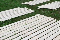 Houten planken op gras stock afbeelding