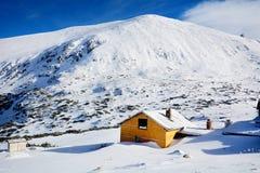 Houten plattelandshuisje op de piek van een Sneeuwberg stock fotografie