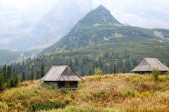 Houten plattelandshuisje twee onder de bergen royalty-vrije stock afbeelding