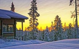 Houten plattelandshuisjehuis bij de winterzonsondergang Royalty-vrije Stock Fotografie