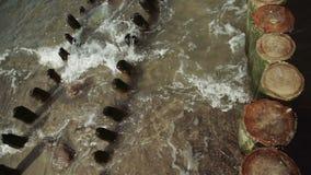 Houten polen in ondiep water van Oostzee met lichte golven stock videobeelden