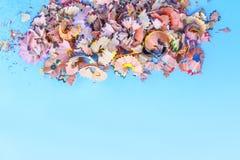 Houten potloodspaanders en kleurrijke crumbs van grafiet van slijper op zachte pastelkleurdocument achtergrond Hoogste mening Ont stock afbeelding