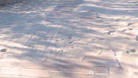Houten promenadeweg op het zandige strand Sporen van dieren en mensen op het zand stock videobeelden