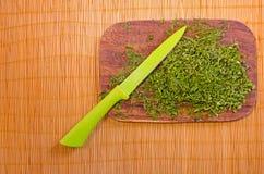 Houten raad met gehakte kruiden en een mes op een bamboemat Stock Foto's