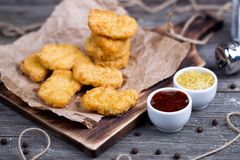 Houten raad met smakelijke kippengoudklompjes en sausen Royalty-vrije Stock Fotografie