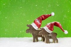 Houten rendier twee: grappige groene en witte Kerstmisachtergrond Stock Foto
