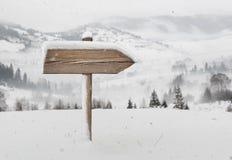 Houten richtingsteken met minder sneeuw en bergen op achtergrond stock foto