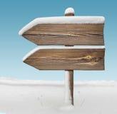 Houten richtingsteken met minder sneeuw en hemel BG two_arrows-one_ stock afbeelding