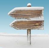 Houten richtingsteken met sneeuw en hemel BG two_arrows-one_direc stock foto