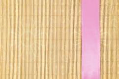 Houten, rieten achtergrond met roze lint Stock Afbeeldingen