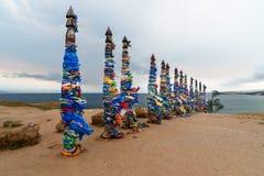 Houten rituele pijlers met kleurrijke linten Hadak op kaap Burkhan Meer Baikal Het eiland van Olkhon Rusland stock afbeelding