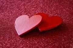 Houten rode harten op rode glanzende achtergrond Stock Foto