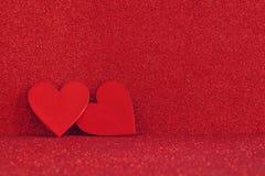 Houten rode harten op rode glanzende achtergrond Stock Afbeeldingen
