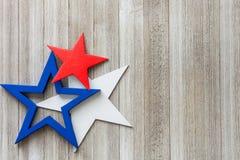 Houten rode, witte en blauwe sterren op een rustieke achtergrond met exemplaarruimte/vierde van Juli-achtergrondconcept stock foto's