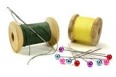 Houten rollen met draden, spelden en naald voor het naaien op een witte achtergrond Stock Foto's