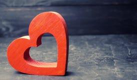 Houten rood hart op een zwarte achtergrond Concept liefde en Romaans De vorm van het hart Orgaanschenking Het verband tussen minn royalty-vrije stock afbeelding