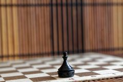 Houten schaakraad en plastic schaakpand, aan boord Stock Foto's