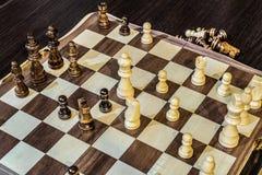 Houten schaakraad en schaakstukken binnen in het spel stock foto