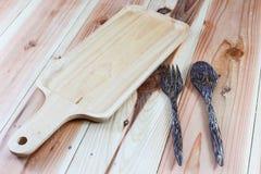 Houten scherpe raad, houten lepels, houten vorken op houten achtergrond Royalty-vrije Stock Fotografie