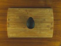 Houten scherpe raad met een avocado stock afbeelding