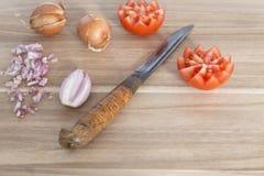Houten scherpe raad met mes, verse uien en tomaten stock afbeelding