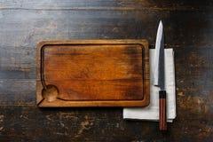 Houten scherpe raadsachtergrond, doekservet en keukenmes Stock Foto's