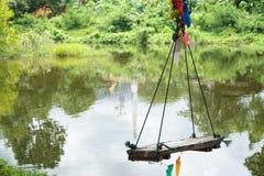 Houten schommelingsstoel dichtbij de rivier Stock Fotografie