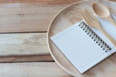 Houten schotel, houten vork en notitieboekje op houten lijst Met tekstruimte Stock Foto