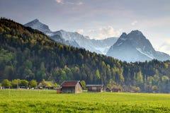 Houten schuren in weide met scherpe Alpspitze, Zugspitze-pieken stock foto