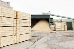 Houten spaanders en gestapelde houten planken voor biomassabrandstof bij zaagmolen stock afbeelding